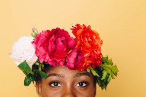 pretty african american woman has a bright flower crown with white pink and orange flowers and green leaves. the picture is taking half way up her face and the background is yellow