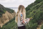 blonde hipster girl in white flowery jumper holds a yellow and purple flower on a hillside