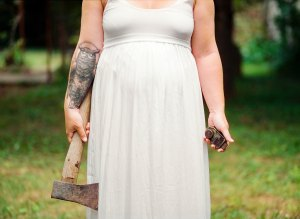 a bigger woman in a white wedding dress holds an axe she has an owl tattoo on her arm she stands outside on the grass