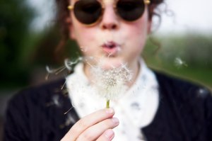 girl with round sunglasses and red hair blowing a dandelion blue sweater white shirt