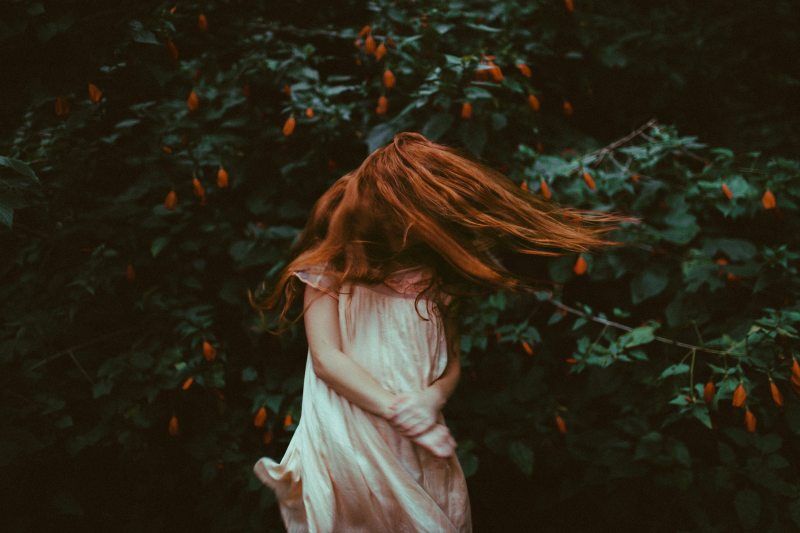 girl with red orange hair wearing a white nightdress swings her hair in front of face while standing in front of a green bush with orange flowers true sex stories tales of sexuality sex confessions