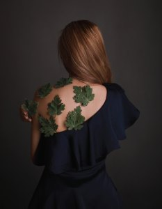 a young woman with red hair faces wearing a one shoulder navy blue dress faces away from camera she has green leaves stuck to her back on her bare skin