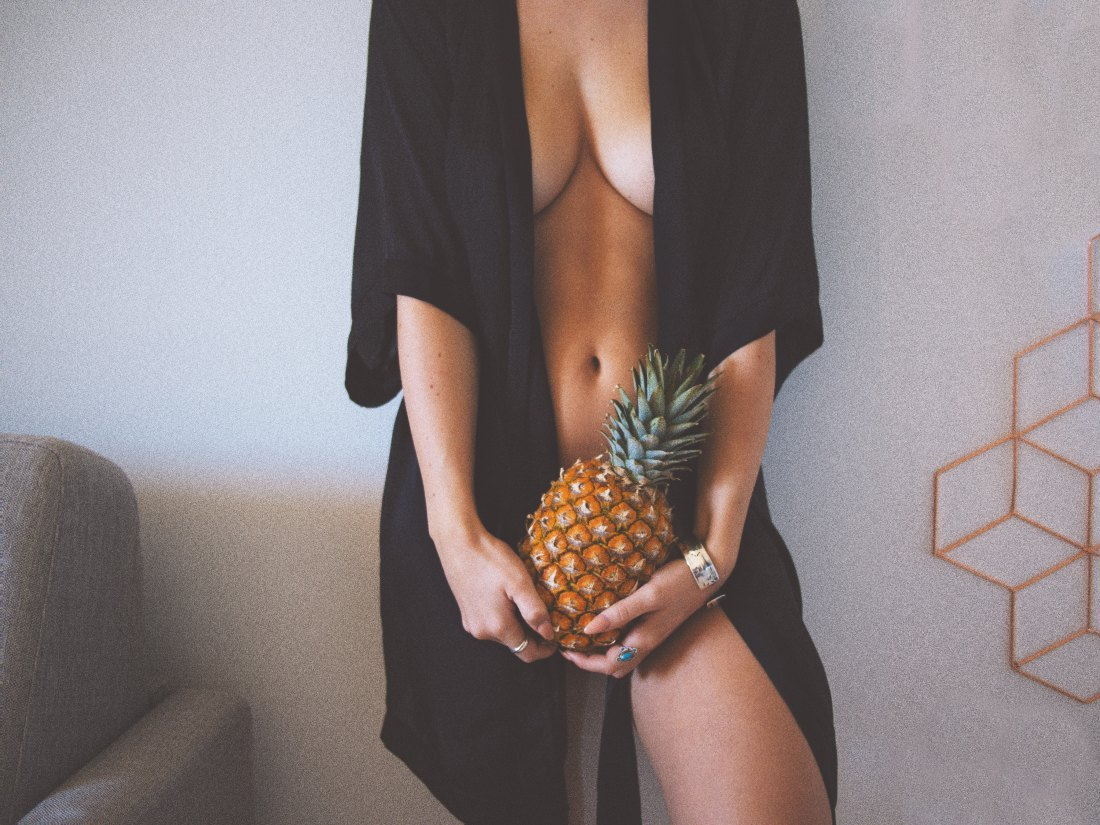 a sensual woman naked with a black kimono holds a pineapple in front of her privates in a white room she is wearing a silver bracelet and a blue ring