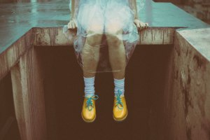 girl sits on building site in plastic poncho and bright yellow boots with blue laces and white socks bare legs spooky
