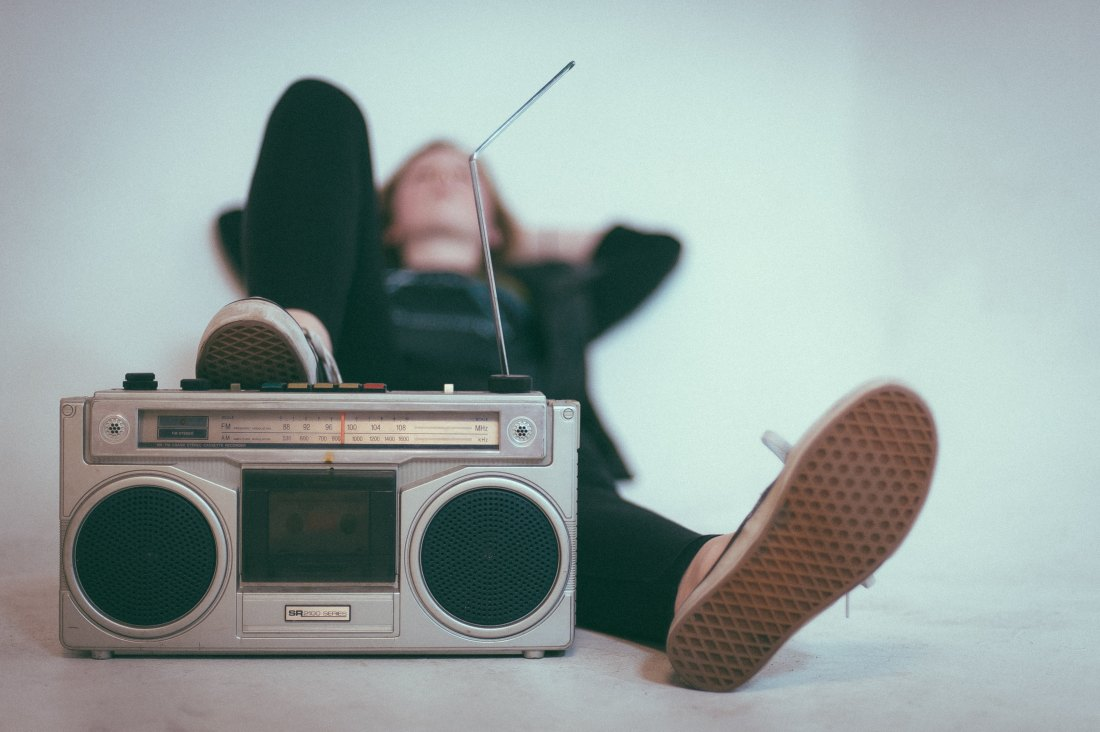 a hipster girl lies on the ground with her arms behind her head and her feet resting on a retro radio, she is wearing black pants and a black sweatshirt
