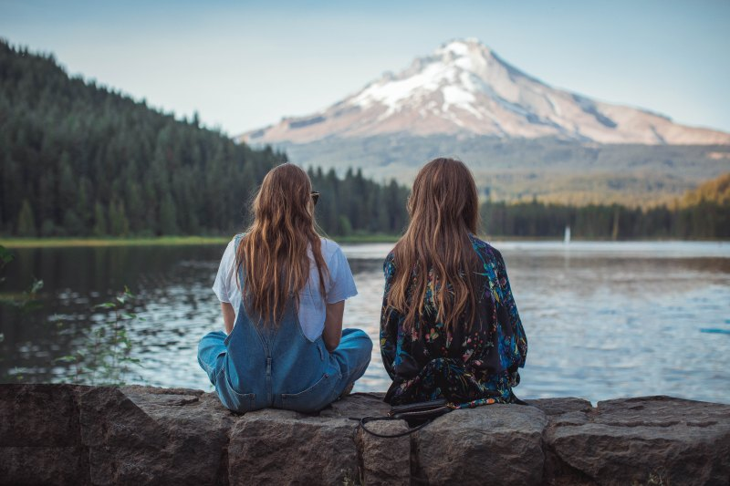 two hipster girls with long hair sit on a wall facing a snowy mountain by a lake