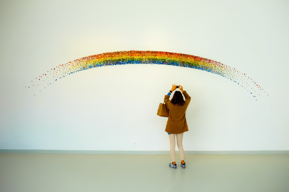 an asian woman in a brown coat and tan trousers takes a photograph of a sparkly rainbow on the wall in an art gallery