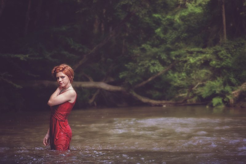 a woman with red hair wearing a red dress stands in a river in front of a tree, her dress is wet and she is holding her shoulder, looking seductively to camera