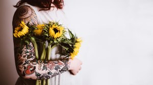 red haired woman with tattoo arm sleeve holds yellow sunflowers in a white dress