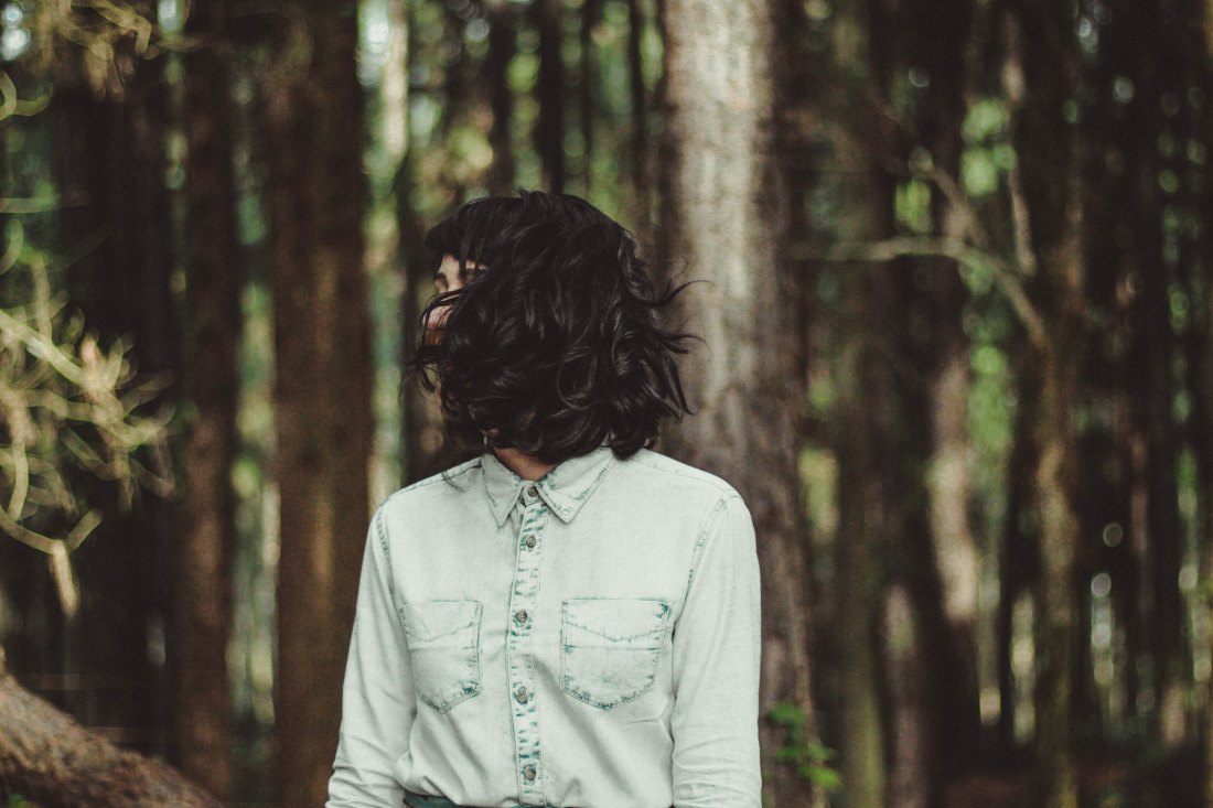 girl with short dark hair over her face in a light denim shirt stands in the forest cowgirl hipster tales of sexuality true sex stories