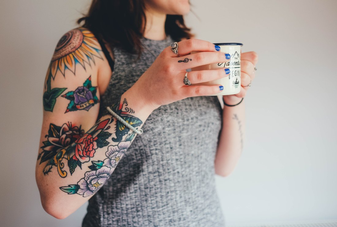 dark haired woman with grey top and arm tattoos finger tattoos drinking a cup of coffee that says the adventure begins here with silver rings and a music note tattooed on her finger